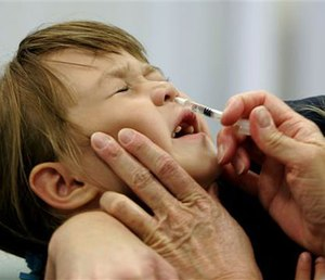 A child reacts as she is given a FluMist influenza vaccination. (AP Photo/Chris Gardner, File)
