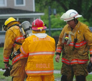 Denmark Fire & Rescue Chief Todd Ross, right, wears a thin pink band on his helmet to remember Bob Riddle, a founding member of the volunteer department who died of brain cancer.