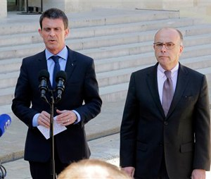 French Prime Minister Manuel Valls, left, and interior minister Bernard Cazeneuve, address the media after a cabinet meeting at the Elysee Palace in Paris, France, Wednesday, April 22, 2015. An Islamic extremist with an arsenal of heavy weapons planned an imminent attack on one or more French churches, France's top security official said Wednesday, announcing the arrest of the man who is also accused in the death of a young mother, Aurelie Chatelain, a 32-year-old Frenchwoman visiting Paris for a training session for her work. (AP Photo/Jacques Brinon)