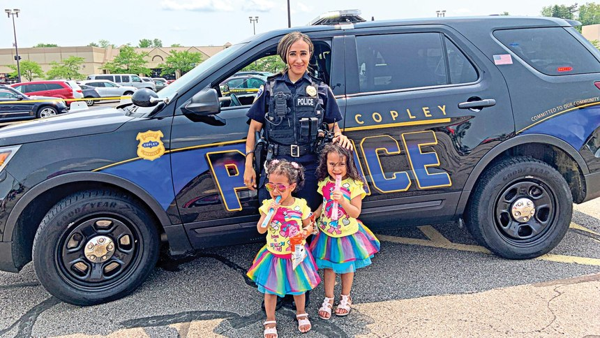 Shendy, shown above at the department's 2019 Bike Rodeo with her nieces, Kenzie and Yazzie Meuanchanh, said she appreciates the opportunity to protect and serve the community, especially children.
