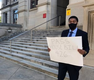 Lawyer Daniel Brown holds a poster calling on Georgia lawmakers to pass a state hate crimes law on Thursday, June 18, 2020 in Atlanta. (AP Photo/Jeff Amy)