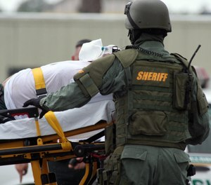 A SWAT Team paramedic treats a suspect that was brought down after taking his wife hostage in the middle of a busy roadway in Florida.