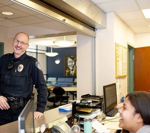 University of Akron Police Officer Kevin Kabellar interacting with students at the front desk of a residence hall. (Photo/Jim Gilbride)