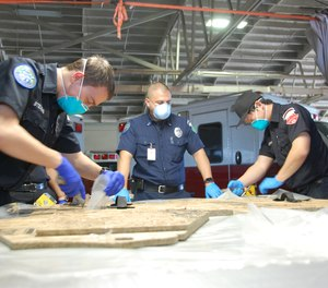 AmbuServe Ambulance Service members are using a wooden template to create their own isolation gowns. The service has produced more than 2,000 gowns and 200 face shields to date.