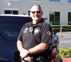 Deputy Chet Parker stands in front of his vehicle