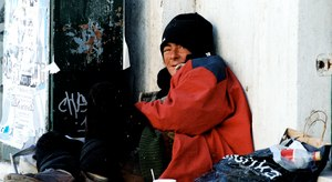 A homeless woman huddles next to a building in Portugal. Women are particularly susceptible to incidences of sexual assault while living on the streets. Image: Pedro Ribeiro Simões/Flickr