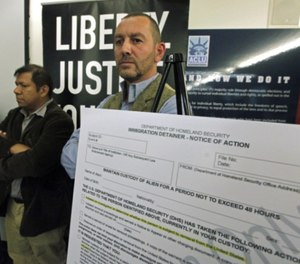 Lead plaintiff Duncan Roy, right, appears at a news conference to announce a federal lawsuit by the American Civil Liberties Union on behalf of arrestees who say they were denied bail because they had federal immigration holds. (AP Photo/Reed Saxon)