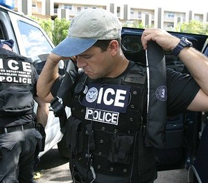 An unidentified Immigrations and Customs Enforcement agent puts on a vest in Tallahassee, Fla. The state is poised to deputize state correctional officers as agents.