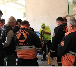 A member of the International Firefighter Relief Mission provides instruction to firefighters in the Republic of Georgia who've just received their first SCBA from the IFRM.
