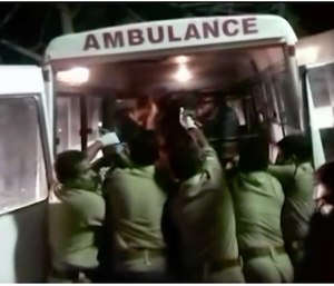 Officials put an injured person into an ambulance following a fire at a temple in Kollam, in the southern Indian state of Kerala, early Sunday.  (Asianet News via AP Video)