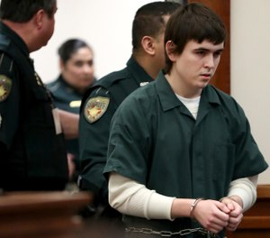 Dimitrios Pagourtzis, the Santa Fe High School student accused of killing 10 people in a May 18 shooting at the high school, is escorted by Galveston County Sheriff's Office deputies into the jury assembly room for a change of venue hearing at the Galveston County Courthouse in Galveston, Texas.  (Jennifer Reynolds/The Galveston County Daily News via AP, Pool)