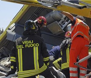 Italian firefighters Vigili del Fuoco inspect the wreckage of two commuter trains after their head-on collision. (Italian Firefighter Press Office via AP)