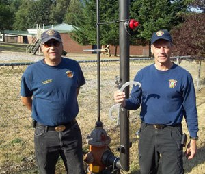 Lt. John Creel (left) and Scott Freeman (right) stand next to an installed Hydrant Snorkel.