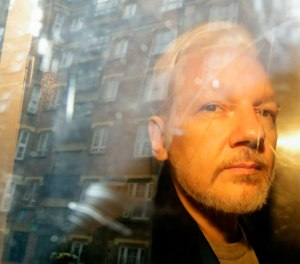 WikiLeaks founder Julian Assange is taken from court, where he appeared on charges of jumping British bail seven years ago, in London. (AP Photo/Matt Dunham, File)