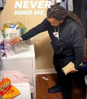 In a screen grab taken from a Facebook video, a man identified in court documents as Joseph Banks of Charlotte poses with a large amount of cash and marijuana in a laundry room.