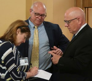 Acting Kansas Corrections Secretary Chuck Simmons, right, confers with recently retired Interim Secretary Roger Werholtz, center, and Jeanny Sharp, the Department of Corrections' spokeswoman, after a meeting of Gov. Laura Kelly and legislative leaders (AP Photo/John Hanna)