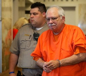 In this May 31, 2016 file photo, Robert Bates, a former Oklahoma volunteer sheriff's deputy who said he mistook his handgun for his stun gun when he fatally shot an unarmed suspect in 2015, is escorted from the courtroom following his sentencing at the courthouse in Tulsa, Okla.