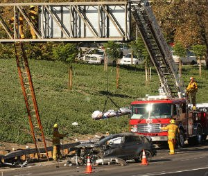 LA firefighters remove the body of a 20-year-old man who landed on a freeway sign after he was ejected from a vehicle during a fatal crash. (Al Seib/Los Angeles Times/TNS)