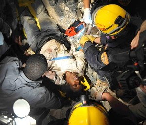 Members of the Los Angeles County Fire Department Search and Rescue Team rescue a Haitian woman from a collapsed building in downtown Port-au-Prince, Haiti, Jan. 17, 2010. The woman had been trapped in the building for five days without food or water. (Photo/Petty Officer 2nd Class Justin Stumberg)