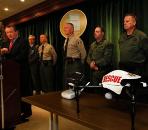Los Angeles Sheriff Jim McDonnell, left, holds a news conference at the Hall of Justice in downtown Los Angeles to announce the recent approval from Federal Aviation Administration authorities for the use of an unmanned aircraft system, at bottom right, on Jan. 12.
