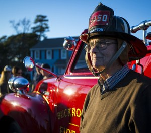Retired Firefighter Robert Joseph Smith Sr. dons his firefighter's helmet at his 90th birthday on Saturday January 25, 2020 in Hampton, VA. Smith's son surprised him on his birthday with the restored antique apparatus he used to drive. (Photo/John C. Clark, Daily Press)