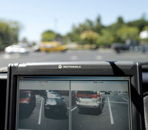 In this Sept.17, 2014 file photo a police vehicle reads the license plates of cars in a parking lot in San Marcos, Calif. (AP Photo/Gregory Bull,File)