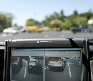 In this Sept.17, 2014 file photo a police vehicle reads the license plates of cars in a parking lot in San Marcos, Calif.