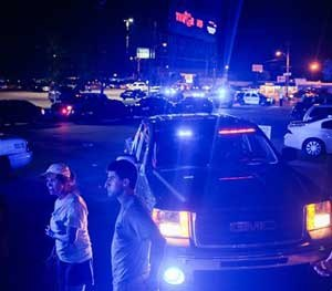 Bystanders look on as emergency personnel respond to the scene of a deadly shooting at the Grand Theatre in Lafayette (La.).