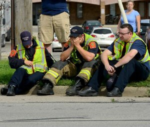 A firefighter puts his head in his hands as he and other firefighters sit on the curb. Dennis Rodeman, a 35-year-old Lansing firefighter has died after being struck by a hit-and-run driver as he collected money for charity. (Dave Wasinger/Lansing State Journal via AP)