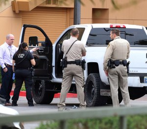 Las Vegas police surround a white pickup truck as they investigate after a pursuit related to the officer-involved shooting that ended at the Golden Nugget hotel-casino on Wednesday, March. 27, 2019, in Las Vegas.  (Bizuayehu Tesfaye/Las Vegas Review-Journal via AP)