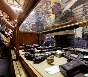 In this Oct. 20, 2017 photo, a case is filled with pistols before an auction of the guns at Johnny's Auction House, where the company handles gun sales for several police departments and the Lewis County Sheriff's Office, in Rochester, Wash. Law enforcement officials around the U.S. are split over the longtime practice among police departments of selling the guns they confiscate. (AP Photo/Elaine Thompson)