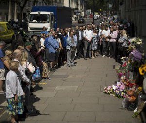 People stand together just before the start of a nationwide minute's silence on the 10 year anniversary of the 7/7 London attacks which killed 52 people, facing in the direction of a plaque and flowers laid at the location of where a suicide bomber blew themselves up during the morning rush hour on a bus in Tavistock Square, London, Tuesday, July 7, 2015. (AP Photo/Matt Dunham)