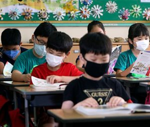 South Korean elementary school students wear masks as a precaution against the MERS, Middle East Respiratory Syndrome, virus as they attend a lesson at an elementary school in Busan, South Korea, Tuesday, June 9, 2015. South Korea is determined to end this week the outbreak of Middle East Respiratory Syndrome, saying upcoming several days will be a critical moment on whether to overcome the medical crisis. (Cha Geun-ho/Yonhap via AP) KOREA OUT