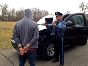 An officer takes a suspect's picture. (Photo courtesy of Mobile Incident Reporting Systems)