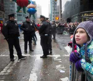 As NYPD officers guard the festivities, a child marvels at the floats and humongous balloons during the Macy's Thanksgiving Day Parade in New York City.  (AP Image)