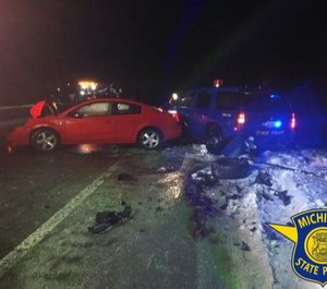 While the trooper was helping the motorist, a passing car hit his cruiser, forcing it into the trooper and motorist (Photo / Michigan State Police)