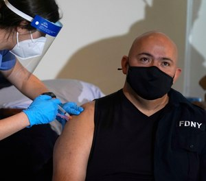 An FDNY member receives the COVID-19 vaccine.
