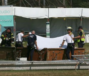 Police and fire officials hold up a sheet a body following a fatal tent collapse at the Prairie Fest in Wood Dale, Ill., Sunday, Aug. 2, 2015. Several people were injured after the tent collapsed at the festival in suburban Chicago, according to the Chicago Tribune. (Stacey Wescott/Chicago Tribune via AP)