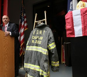 The bunker coat and helmet of FDNY chaplain Mychal Judge are displayed during a September 11, 2011 memorial service.