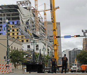 New Orleans Fire Department personnel stand by the scene of the Hard Rock Hotel in New Orleans.