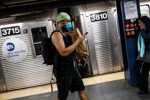 A commuter wears a face mask in the New York City transit system. Image: AP Photo/John Minchillo