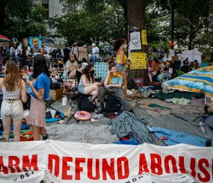 Protesters rest on a grassy area surrounded by signs calling for the changes and abolition of police forces at an encampment outside City Hall in New York.