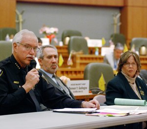 Mike Heal, left, police chief for the city of Aztec, N.M., testifies in support of a state bill that would take away guns temporarily under court orders from people who are considered a danger to themselves or others, in Santa Fe, N.M. Heal says the bill from Democratic state Reps. Daymon Ely, center, and Joy Garratt, right, provides a new tool to keep school students safe.