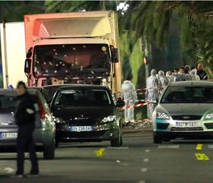 Forensic officers stand near a truck with its windscreen riddled with bullets, that plowed through a crowd of revelers who'd gathered to watch the fireworks in the French resort city of Nice. (AP Photo/Claude Paris)