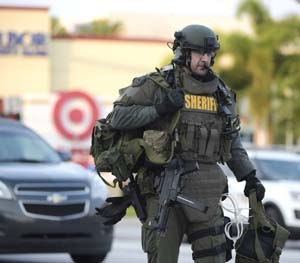 An Orange County Sheriff's Department SWAT member arrives to the scene of a fatal shooting at Pulse Orlando nightclub in Orlando, Fla., Sunday, June 12, 2016.
