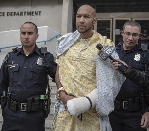 In this Oct. 24, 2015, file photo, Davon Lymon, center, an ex-convict charged in the shooting of an Albuquerque police officer, is escorted by Albuquerque police officers after being released from the hospital in Albuquerque, N.M. (Roberto E. Rosales/The Albuquerque Journal via AP File)
