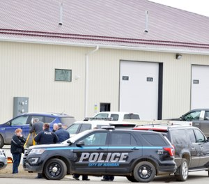 Mandan, N.D. Police Deputy Chief Lori Flaten, left, and other law enforcement personnel stand outside the scene on the south side the RJR Maintenance and Management property in Mandan, N.D., Monday, April 1, 2019. (Mike McCleary/The Bismarck Tribune via AP)
