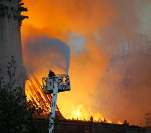 A firefighter douses flames at the Notre Dame cathedral fire in April 2019.