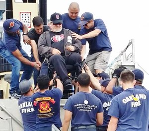Oakland Firefighters Random Acts volunteers helped to carry wheelchair-bound Veterans at the 2018 Wheelchair Regatta at the Encinal Yacht Club in Alameda. (Photo/courtesy https://www.facebook.com/Oakland-Firefighters-Random-Acts-381744737537/?tn-str=k*F)