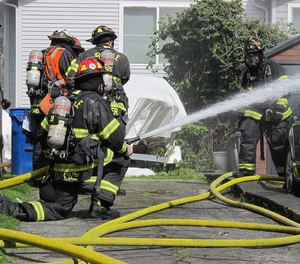 The proper use of the structural firefighting protective ensemble during fire suppression operations and the decontamination of personnel as they exit the hazard area have become of paramount concern for firefighters and officers alike. (AP Photo/Bebeto Matthews)